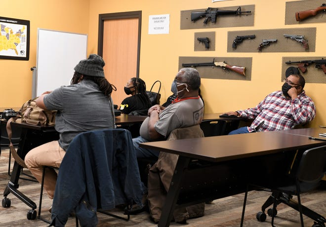 Gun owners listen to trainers at CrossRoads Shooting Sports during a conceal carry training session that the National African American Gun Association held in Johnston, Iowa, on Feb. 20, 2021.