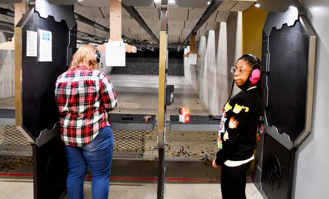 Deaonda Bradley, right, waits after firing practice shots during a National African American Gun Association training session at CrossRoads Shooting Sports in Johnston, Iowa, on Feb. 21, 2021.