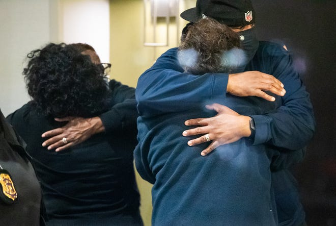 People hug after learning that their loved one is safe after a person shot and killed 8 people inside a FedEx building Friday, April 16, 2021 in Indianapolis.
