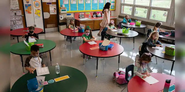 A teacher walks among the masked students sitting in a socially distanced classroom session at Medora Elementary School.