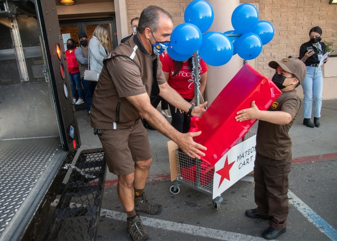 Six-year-old Mateo helps UPS driver Dave Cundari load packages into a UPS truck during a ceremony at the Macy's at Sherwood Mall in Stockton on April 21, 2021. Make-A-Wish Northeastern and Central California and Northern Nevada and Macy's teamed up with UPS to give Mateo, who's battling leukemia, an experience of being a delivery person. Mateo's wish is to be a mailman.