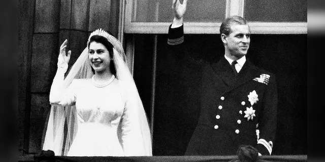 Queen Elizabeth and her husband the Duke of Edinburgh wave to the crowds on their wedding day, from the balcony of Buckingham Palace in London.