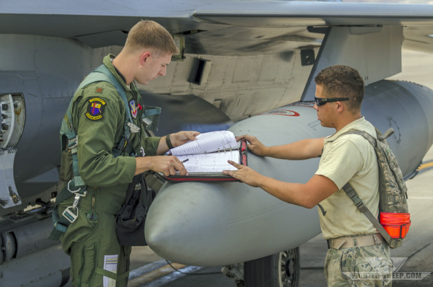 "Major Michael ""Double"" Blauser, and Instructor Pilot with the 16th Weapons Squadron (WPS) looks through the maintenance log book prior to launching for a Weapons School sortie."