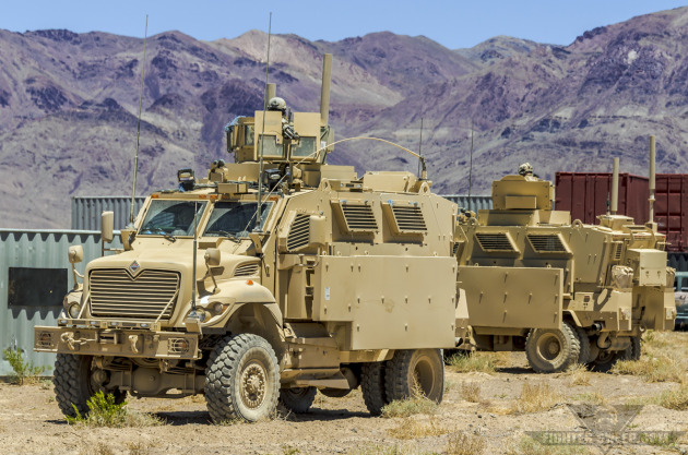 Two U.S. Army MRAPs carrying Special Forces soldiers move through a target area during an Advanced Integration training scenario.