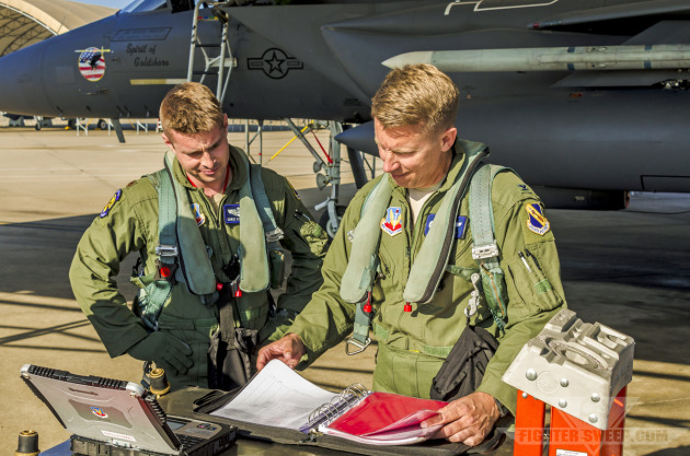 """""""Wyatt"""" and """"Moon"""" read over the maintenance logbook prior to launch for a Large Force Exercise at Seymour Johnson AFB, NC."""