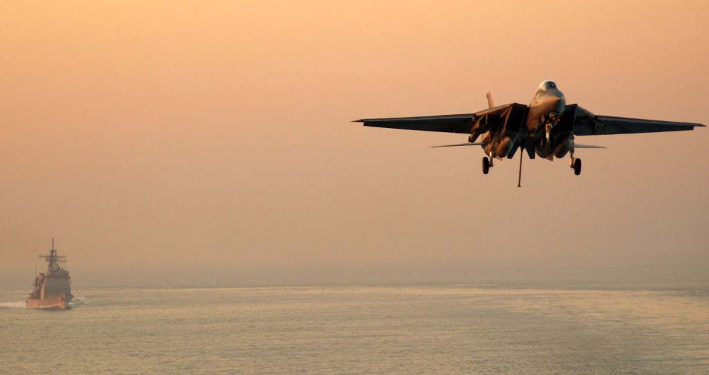 An F-14D Tomcat prepares for an arrested landing aboard the aircraft carrier USS Theodore Roosevelt as the guided-missile cruiser USS San Jacinto conducts plane guard duties, in the Persian Gulf, Jan. 6, 2006. Roosevelt and embarked Carrier Air Wing 8 are underway on a regularly scheduled deployment conducting maritime security operations. U.S. Navy photo by Airman Apprentice Nathan Laird