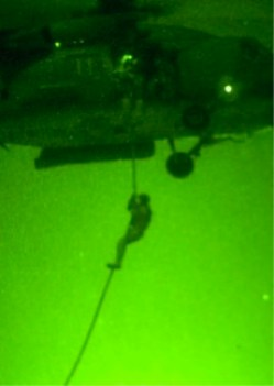 A helicopter from HSC-84 conducts night fast rope training with SOF personnel.