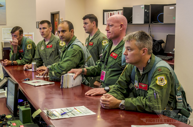 """Cheetah,"" ""Glover,"" ""T-Bone,"" ""Chowmi,"" and other pilots from the 64 AGRS get their step brief before walking out to their jets for a training mission at Nellis AFB, Nevada."