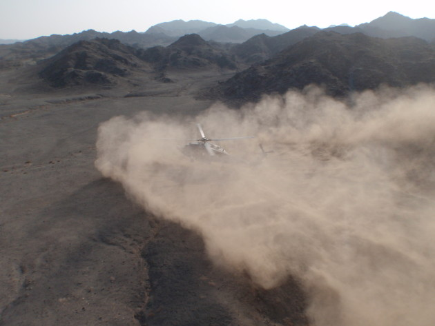 An aircraft from HSC-84 lands in light brownout conditions.