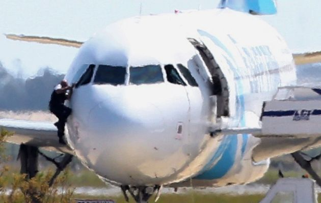 A member of EgyptAir 181's crew escapes the aircraft using a cockpit window. (Photo courtesy of AP/Reuters)