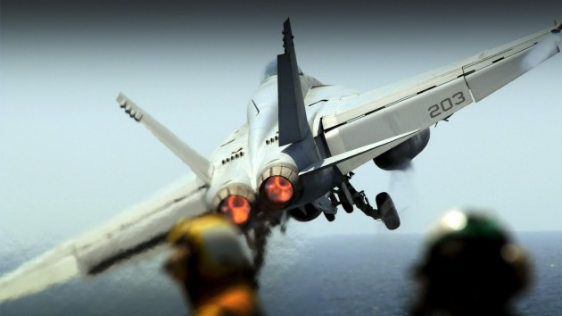 A Boeing F/A-18E Super Hornet takes off from an aircraft carrier. (Photo courtesy of wallconvert.com)