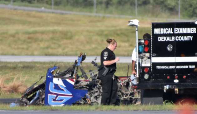 Officials investigate a crash at an Atlanta-area airshow. The pilot was killed. (Photo COurtesy of the Houston Chronicle)
