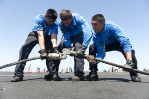 Sailors participate in the cross deck pendant swap during flight deck Olympics aboard the aircraft carrier (US Navy)