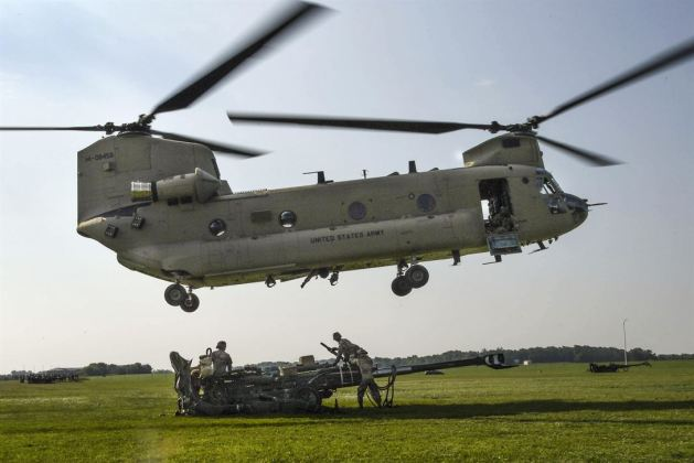 Soldiers sling-load M777 Howitzers using Boeing CH-47 Chinook helicopters