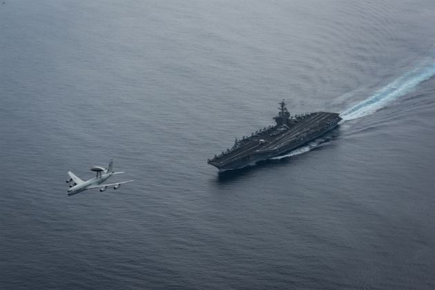Air Force E-3 Sentry over the aircraft carrier USS Theodore Roosevelt CVN 71