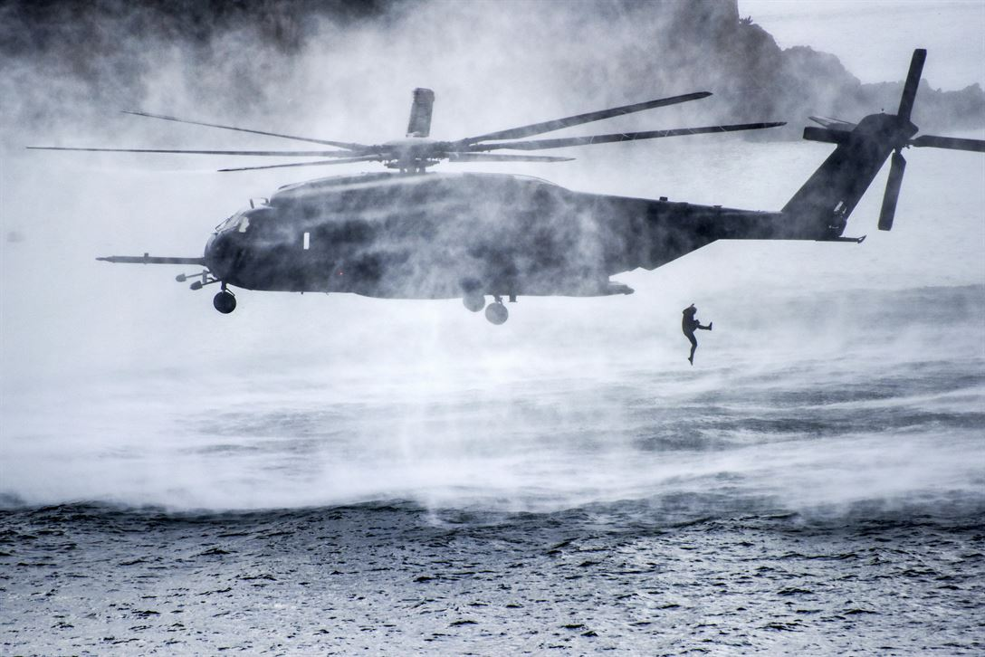 service member jumps from a Navy MH-53E Sea Dragon helicopter during a mine warfare training