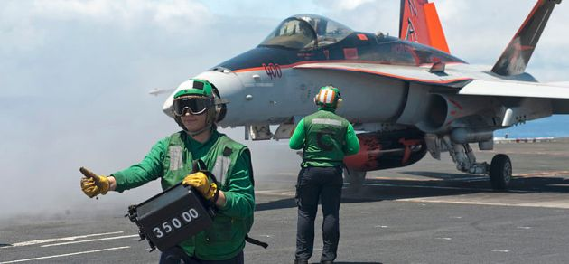 Airman Raven Romero gives the thumbs up as he verifies the weight of an FA-18C Hornet before launching
