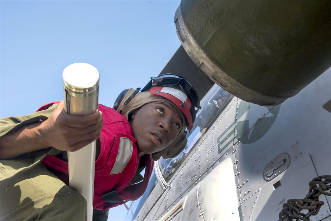 Marine Corps Cpl. Austin McClure places a rocket on an H-1W Cobra