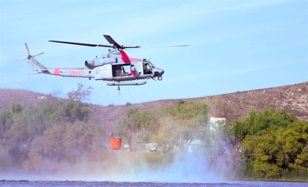 UH-1Y Venom from Marine Light Attack Helicopter Squadron (HMLA) 267 takes off with a load of water from Lake O'Neil at Marine Corps Base Camp Pendleton