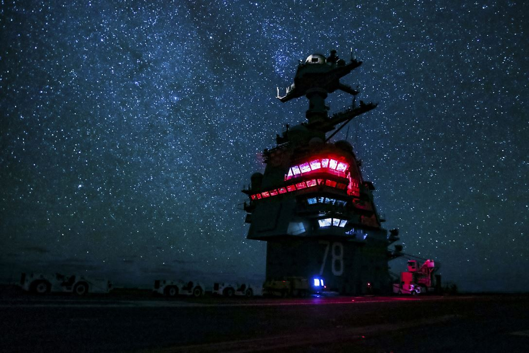 aircraft carrier USS Gerald R. Ford travels in the Atlantic Ocean at night