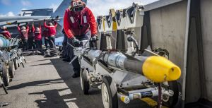Seaman Charles Joseph transports a missile on the flight deck of the aircraft carrier USS Carl Vinson