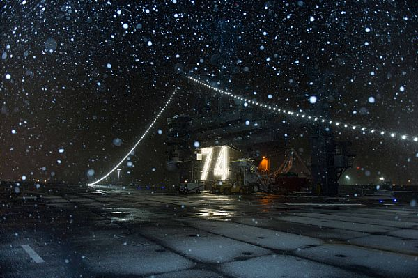 Snow falls on the flight deck of the aircraft carrier USS John C. Stennis (CVN 74) on Christmas Eve