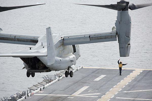 Aviation Boatswain's Mate 2nd Class Jamel Agee signals an MV-22 Osprey