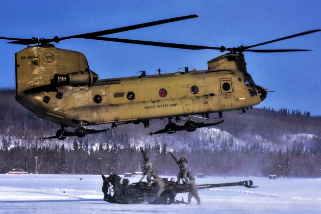 Soldiers Attach a 155 mm Howitzer to a CH-47 Chinook Helicopter