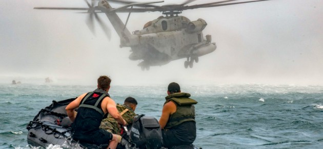 U.S. Marines depart the drop zone after dropping military members into the ocean during helicopter casting training