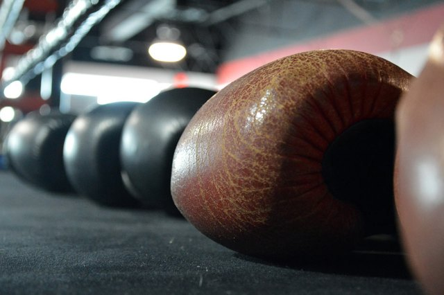 Boxing gloves laid out on the gym mat.