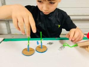 rubber band car, stem, steam. Figment Creative Labs, Austin Texas, engineering, kids activities, Newton's law of motion, elasticity, motion, DIY, mechanics,