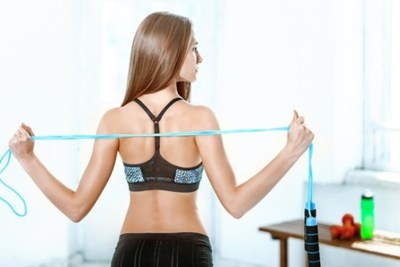 57281382 - the back view of muscular young woman athlete with a skipping rope on white background.