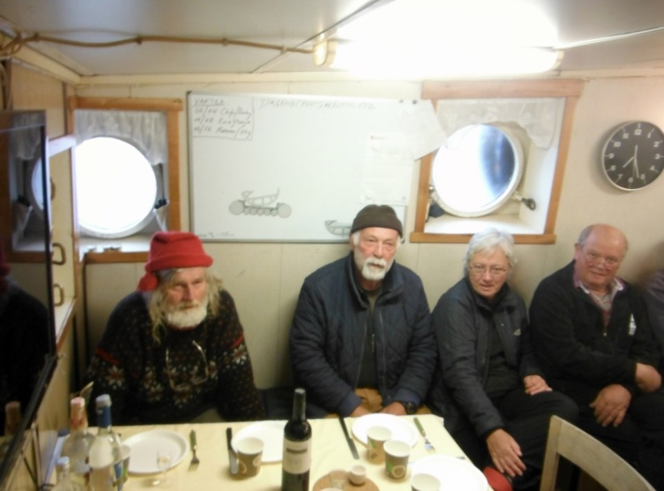 Seal Dinner aboard Tandberg Polar. Note Father Christmas; Glenna and Ann from Gjoa.