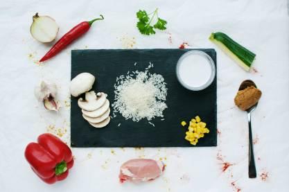 Foto met ingredienten peper knoflook paprika pindakaas rijst courgette kip kokosmelk champignons