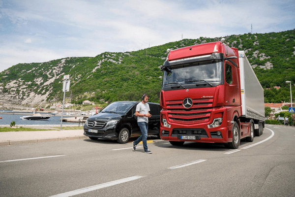 A man crossing the road in front of the The Mercedes-Benz Atros 2019