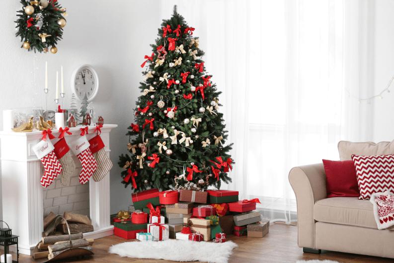 Cây thông Noel treo nhiều nơ đỏ, quả cầu, dưới là nhiều hộp quà đặt cạnh lò sưởi, một bên là ghế sofa.