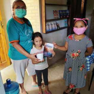 Grandes y pequeños recibiendo el libro misionero La Mayor Esperanza