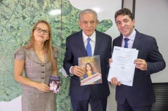 A diretora do Quebrando o Silêncio ao lado do prefeito Ires Rezende que segura o material da campanha, enquanto o vereador Cabo Senna exibe a lei assinada.