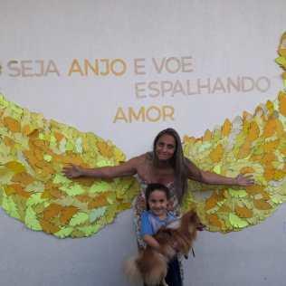 Queila Fernandes Souza Mello e filha Danyelle posam para foto nas asas amarelas.