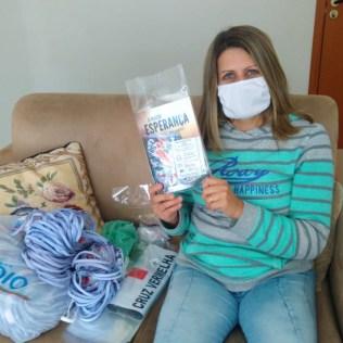 voluntária empacota livros, máscaras e bilhetes para quem participar da campanha
