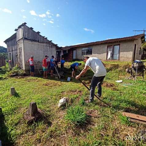 Fiéis capinam e preparam terreno para construção da nova casa.[Foto: Harry Metzner].