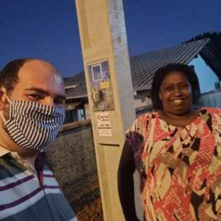 Pastor Harry e dona Ester posam para foto ao lado do novo poste de energia elétrica.[Foto: Harry Metzner].