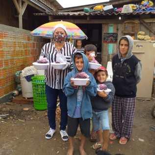 Crianças recebem marmitas de voluntária (Foto: Divulgação)