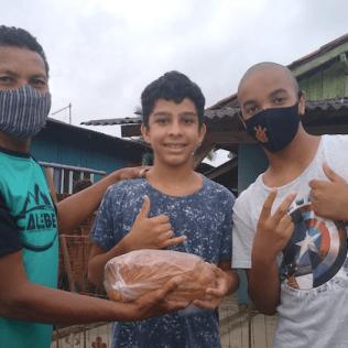 Voluntários entregam pão caseiro para jovem da comunidade. [Foto: Reprodução].