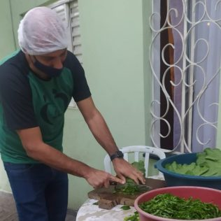 Pastor Caio Almeida, líder da ASA, participa da preparação das refeições (Foto: Gabriela Victório).