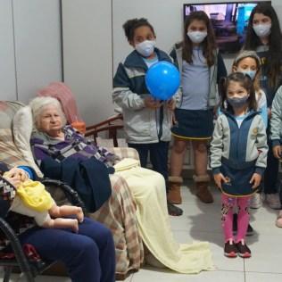 Idosos acompanham apresentação musical das crianças. Todos os moradores e cuidadores estão vacinados contra o coronavírus
