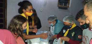 Voluntários durante preparação das marmitas. [Foto: Reprodução].