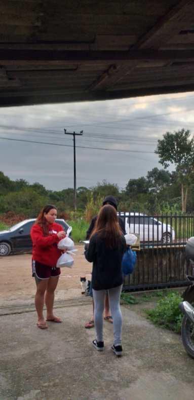 Voluntários entregam marmitas para moradora. [Foto: Reprodução].