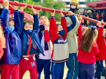 Crianças se divertem ao conhecerem funcionalidades das viaturas dos bombeiros. [Foto: Reprodução].