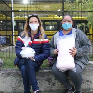 Eliane Ribeiro [à esquerda] e Luciene Oliveira posam para foto com café da manhã e cobertor recebidos dos estudantes. [Foto: Paulo Ribeiro].